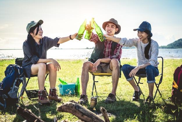 Groupe de jeunes amis asiatiques profiter de pique-nique et faire la fête au lac avec sac à dos de camping Photo Premium
