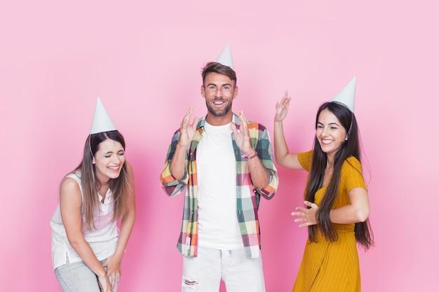 Groupe de jeunes amis heureux s'amuser sur fond rose Photo gratuit