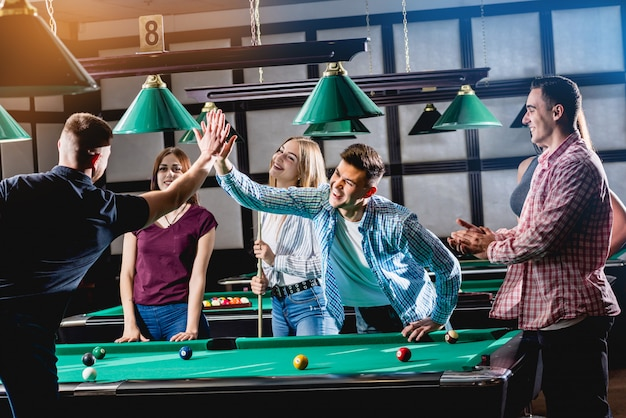 Groupe De Jeunes Amis Joyeux Jouant Au Billard. Photo Premium