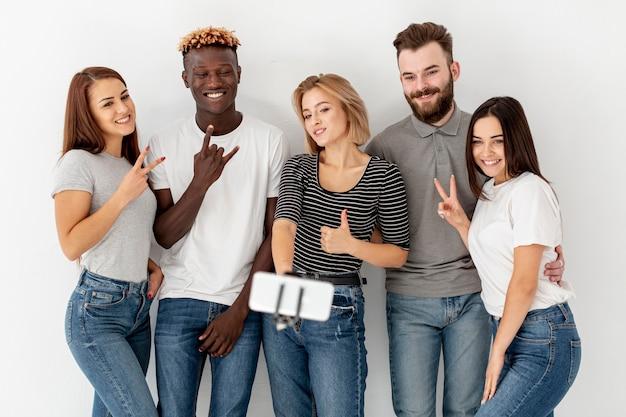 Groupe de jeunes amis prenant des selfies Photo gratuit