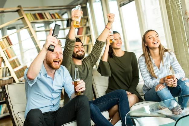 Groupe de jeunes amis regardant la télévision, buvant du cidre et s'amusant dans la chambre Photo Premium