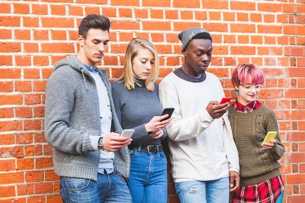 Groupe de jeunes amis avec les téléphones intelligents Photo Premium