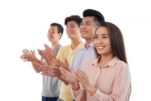 Groupe de jeunes asiatiques dans la rangée et applaudissements Photo gratuit