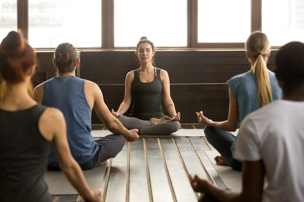 Groupe de jeunes assis à sukhasana Photo gratuit