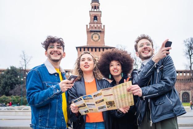 Groupe De Jeunes Beaux Amis Multiethniques Touristiques En Plein Air à L'aide De La Carte Photo Premium