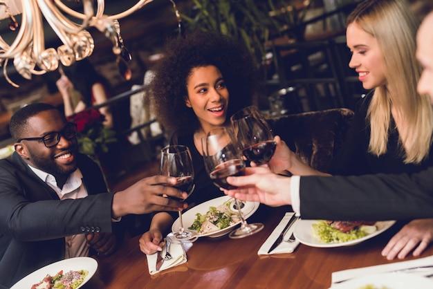 Groupe de jeunes buvant du vin dans un restaurant. Photo Premium