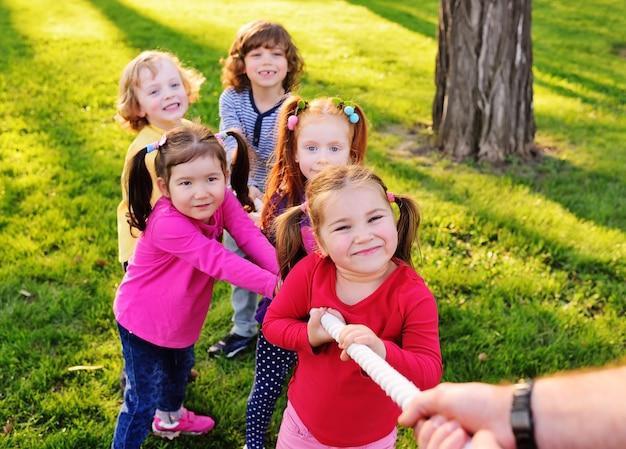 Un groupe de jeunes enfants d'âge préscolaire joue un bras de fer dans le parc. Photo Premium