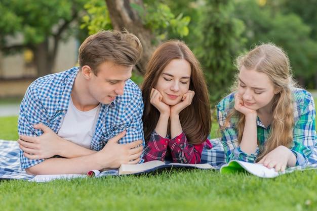 Groupe de jeunes étudiants apprenant dans un parc Photo gratuit