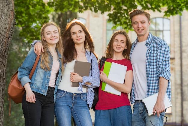 Groupe De Jeunes étudiants Devant Le Bâtiment De L'école Photo gratuit