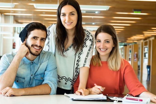 Groupe de jeunes étudiants étudient ensemble dans la bibliothèque. Photo Premium