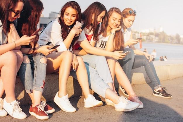 Groupe de jeunes filles heureuse, vrais amis, étudiants, utilisation, mobile, à, rue ville Photo Premium