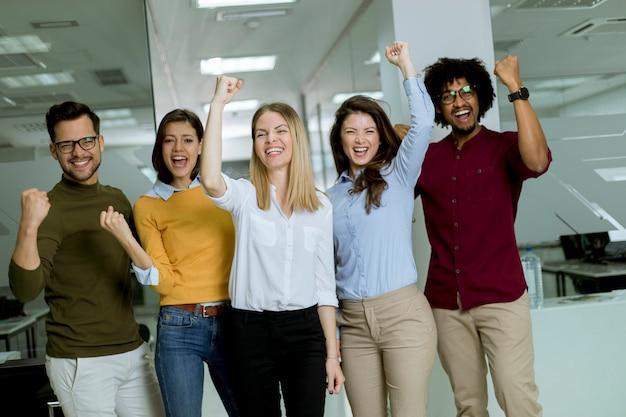 Groupe de jeunes gens d'affaires excités avec les mains debout dans le bureau Photo Premium
