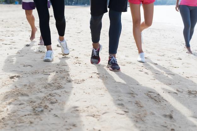 Groupe de jeunes gens courir sur la plage pieds sport gros plan jogging travailler entraînement en équipe Photo Premium