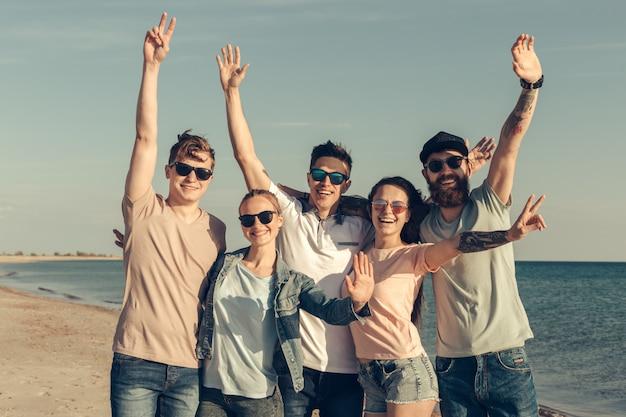 Groupe de jeunes gens profitent d'une fête d'été à la plage Photo Premium