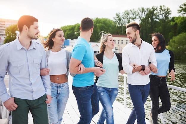 Groupe De Jeunes Gens Souriants Et Réussis En Vacances Sur Le Quai. Photo Premium