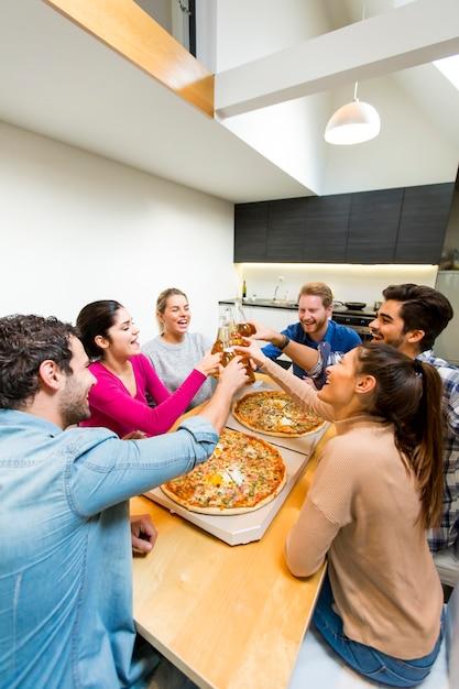 Groupe de jeunes heureux mangeant des pizzas et buvant du cidre dans un intérieur moderne Photo Premium