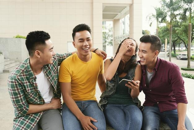 Groupe de jeunes hommes asiatiques et fille assis ensemble dans une rue urbaine et rire Photo gratuit