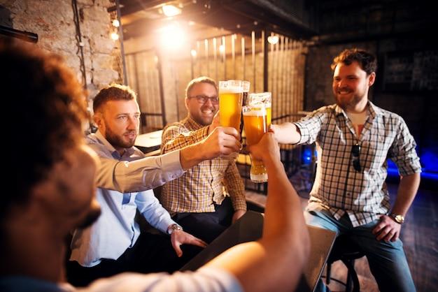 Groupe De Jeunes Hommes Positifs Grillage Avec Une Bière Dans Le Pub Ensoleillé Après Le Travail. Photo Premium