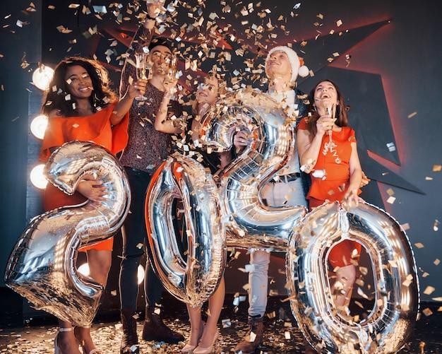 Un groupe de jeunes multinationales jolies s'amusant à lancer des confettis lors d'une fête. célébration de 2020. Photo Premium