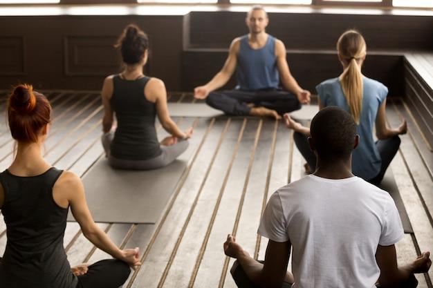 Groupe de jeunes sportifs assis à l'exercice de sukhasana Photo gratuit
