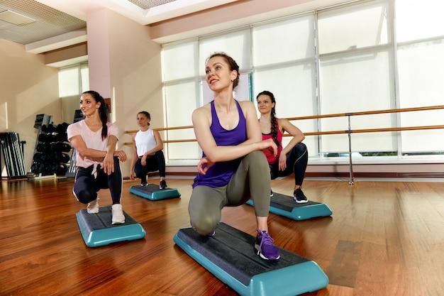 Un groupe de jeunes sportifs en vêtements de sport, dans une salle de fitness, en train de faire des pompes ou des planches dans la salle de sport. concept de fitness en groupe, entraînement de groupe, motivation Photo Premium
