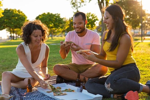 Groupe de joyeux amis fermés en train de manger une pizza dans le parc Photo gratuit