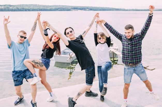 Groupe de joyeux amis insouciants dansant près du lac Photo gratuit