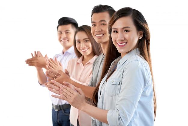 Groupe De Joyeux Asiatiques Debout Dans La Rangée Et Applaudissant Des Mains Photo gratuit