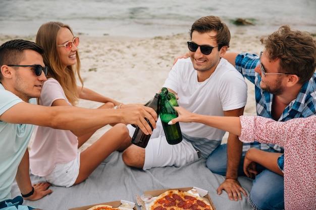 Groupe de meilleurs amis faisant un toast, boire de la bière tout en s'amusant sur la plage Photo gratuit