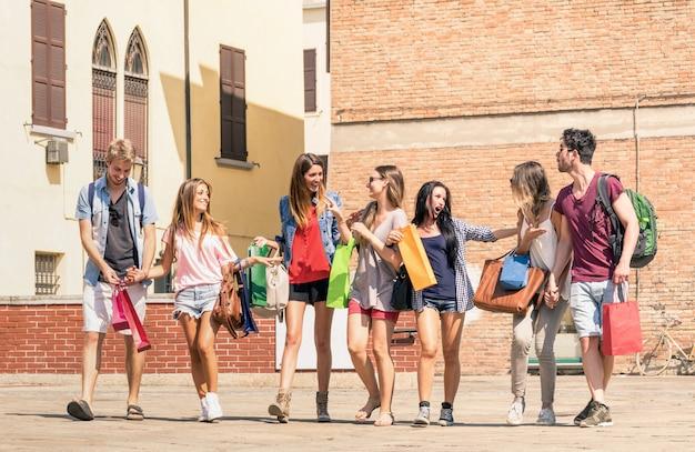 Groupe de meilleurs amis heureux avec des sacs à provisions marchant dans le centre-ville Photo Premium