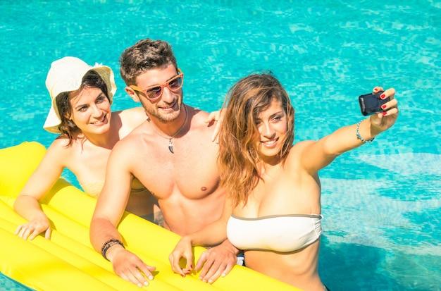 Groupe de meilleurs amis prenant selfie à la piscine sur le matelas pneumatique jaune Photo Premium
