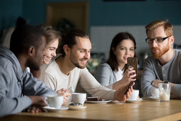 Groupe multi-ethnique d'amis parlant et utilisant un smartphone lors d'une réunion Photo gratuit