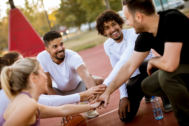 Groupe multi-ethnique de basketteurs reposant sur le court Photo Premium
