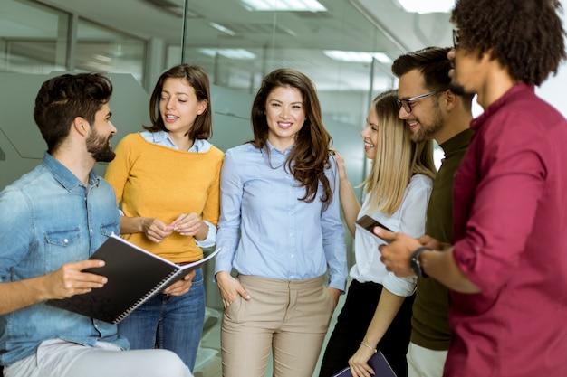 Groupe multiethnique de jeunes debout dans le bureau moderne et de brainstorming Photo Premium