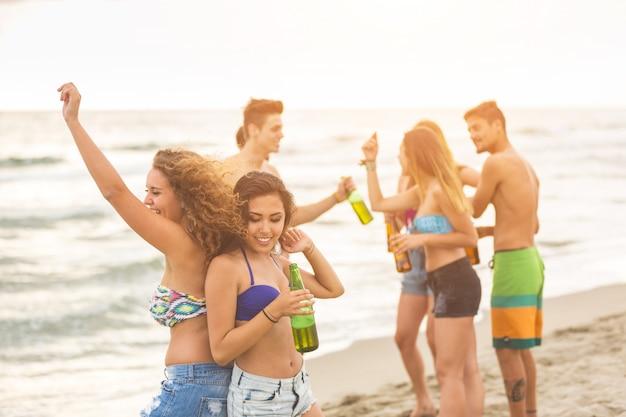Groupe multiracial d'amis ayant une fête sur la plage Photo Premium