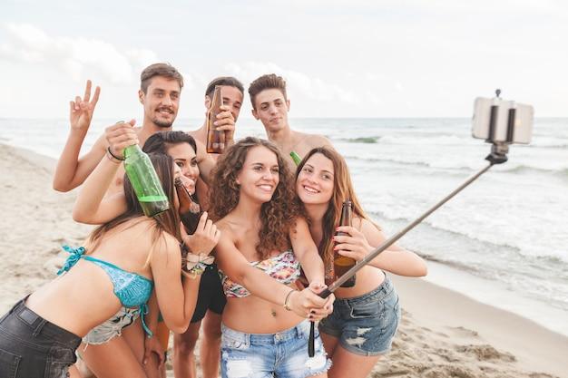 Groupe multiracial d'amis prenant selfie sur la plage Photo Premium