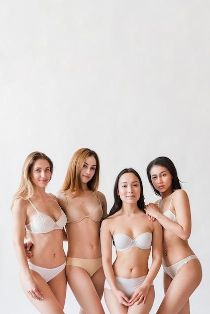 Groupe multiracial de femmes séropositives posant en lingerie Photo gratuit