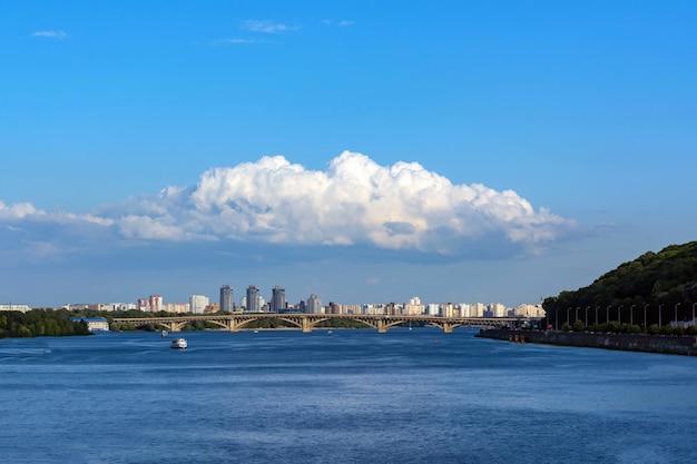 Un groupe de nuages au-dessus de la ville contre un ciel dégagé et une rivière. Photo Premium