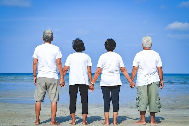 Le Groupe De Personnes âgées S'est Tenu En Arrière, Tenant La Main, Vêtu D'une Chemise Blanche, Visitant La Mer. Photo Premium