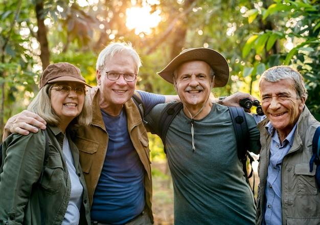 Groupe de personnes âgées trekking dans la forêt Photo Premium