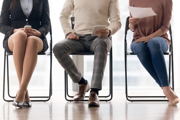 Groupe de personnes en attente d'un entretien d'embauche, assis sur des chaises Photo gratuit