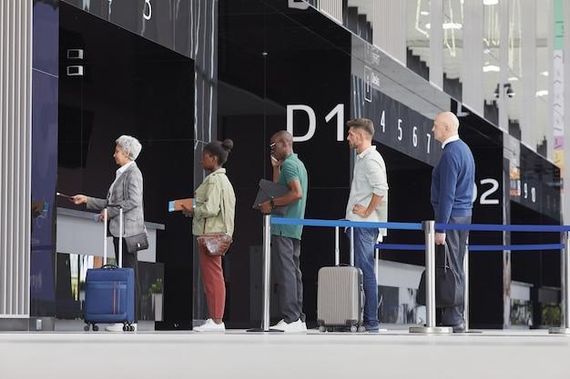 Groupe De Personnes Avec Des Bagages Debout Dans Une File D'attente Près De La Porte D'embarquement à L'aéroport Photo Premium