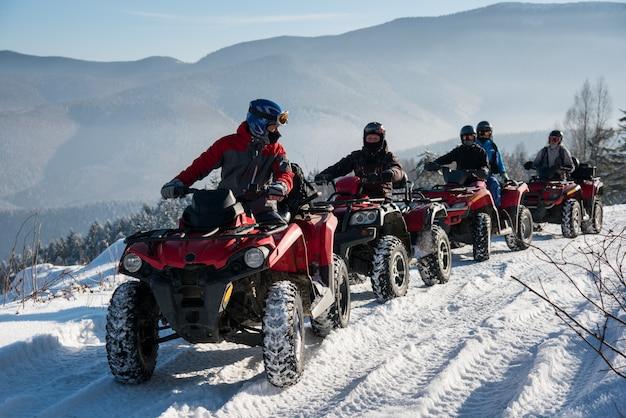 Groupe de personnes conduisant des quads hors route sur la neige au sommet de la montagne en hiver Photo Premium