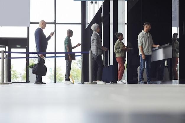 Groupe De Personnes Debout Dans Une Rangée Et Acheter Des Billets Pour L'avion à L'aéroport Photo Premium