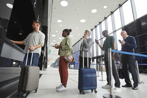 Groupe De Personnes Debout Dans Une Rangée à La Billetterie De L'aéroport Photo Premium