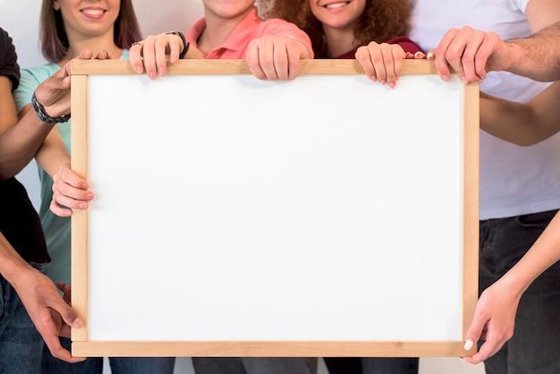 Groupe de personnes détenant un cadre photo blanc vide avec pensionnaire en bois Photo gratuit