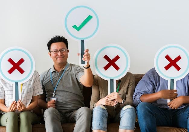 Groupe de personnes détenant des icônes vraies et fausses Photo Premium