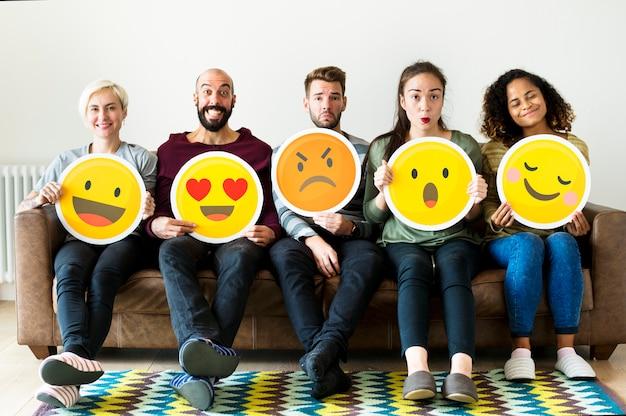 Groupe de personnes diverses détenant des icônes d'émoticônes Photo Premium