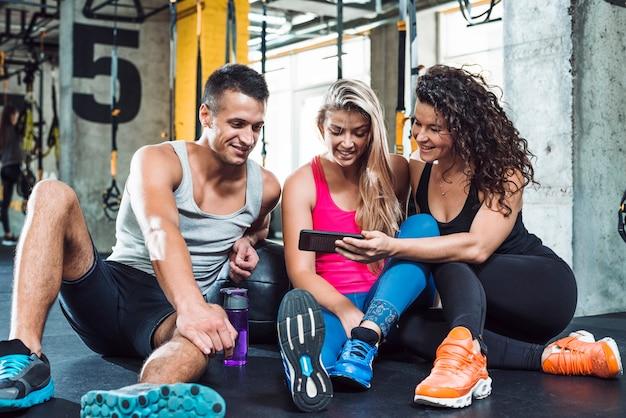 Groupe, personnes, regarder, téléphone portable, dans, club fitness Photo gratuit