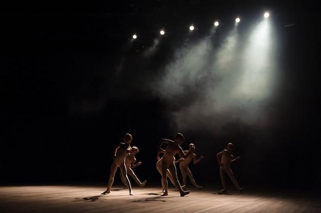 Un groupe de petits danseurs de ballet répète sur scène avec lumière et fumée Photo Premium